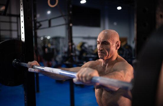 Bald senior athlete taking barbell from rack