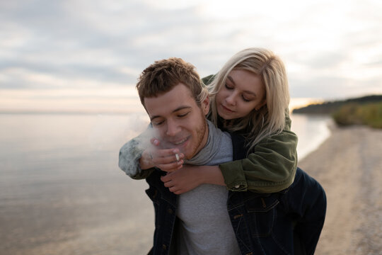 Loving millennial couple smoking joint strolling on cold seashore
