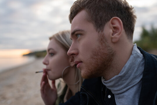 Young hipsters smoking cannabis on empty cold seashore