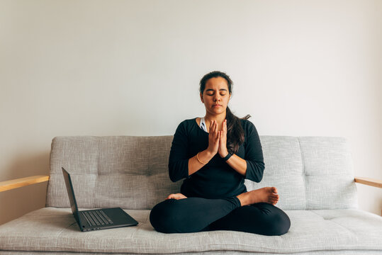 Latin woman sitting doing yoga watching an online class indoors. Yoga at home concept. Copy space