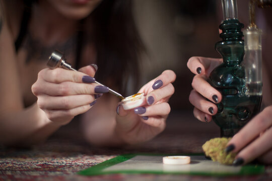 Women with nicely manicured fingernails use a titanium dabber tool to scoop concentrated cannabis wax, shatter, oil out of silicone container to smoke in a chilled custom blown glass water pipe design