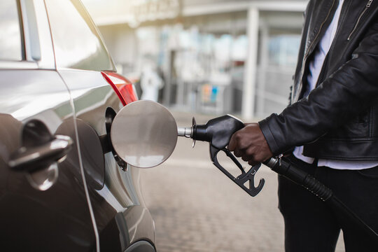 Cropped close up image of unrecognizable African businessman in casual wear, rholding in hand filling gun and refueling his luxury car with gasoline at the petrol station