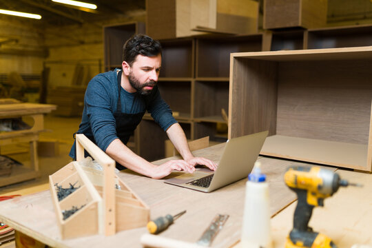 Hispanic man in his 30s typing on a laptop in his woodshop