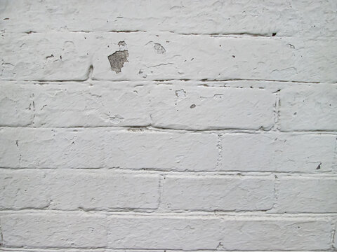 White brick wall painted with old paint. Solid light background with old age damage.