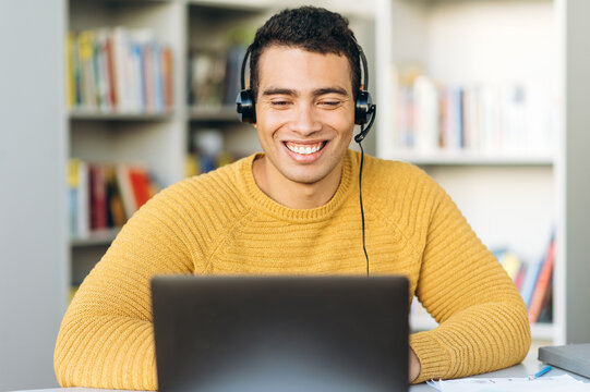 Confident male employee at online video meeting. Handsome smiling hispanic freelancer guy uses laptop, wearing headphones, discussing work questions with colleagues