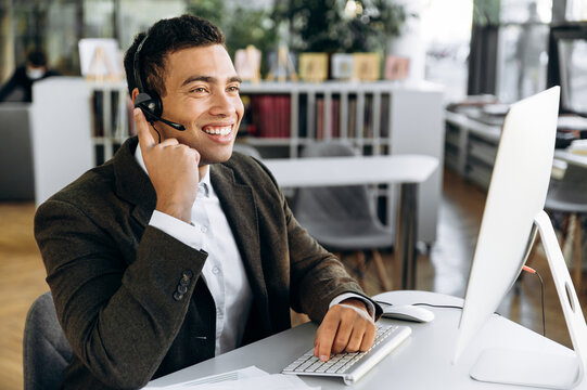 Joyful employee is consulting people, sitting in modern office. Successful hispanic business wearing headset man work as call center operator, communicate with clients, conducts online meeting