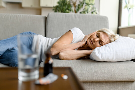 Upset middle aged Caucasian woman lying on sofa with headache due to illness, stress, overwork, need a rest sleep and pills