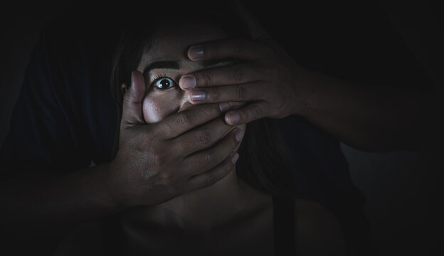 A man who covers his mouth women with his hand Human trafficking concept Violence victims