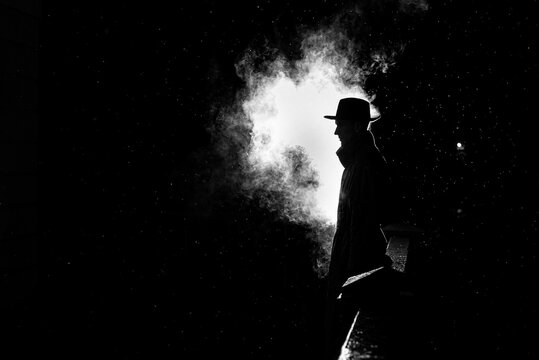 dramatic silhouette of a dangerous man in a hat at night in the rain in the city