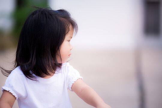 Candid adorable Asian little kid girl is wearing a white shirt, looking at the left side. Sweet smile in summer or spring. Photos in the right half of the page. Baby child age 3 - 4 years old.