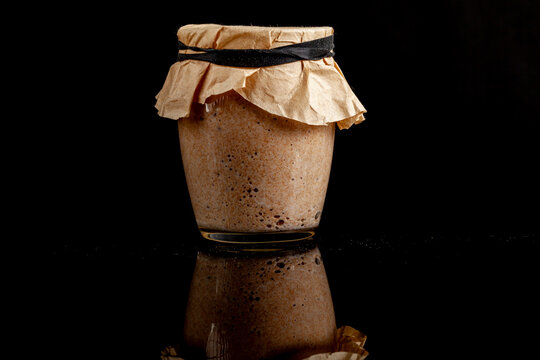 A glass cup of sourdough starter culture for homemade bread making. The cup is covered with brown filter paper and tightened with elastic band. Active culture creates bubbles. On reflective surface.