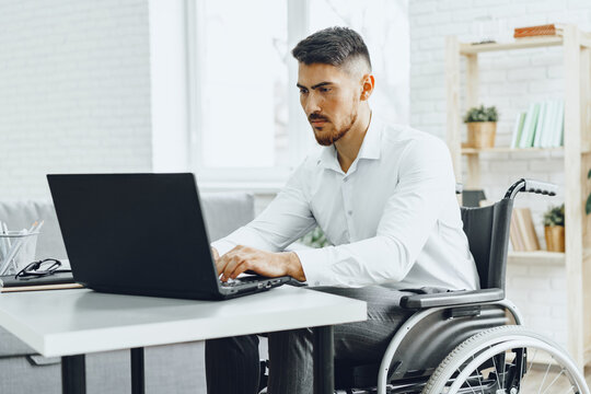 Serious concentrated man in wheelchair using his laptop for work / seeking a job in internet