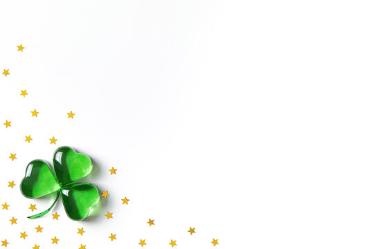 Shamrock symbol made of green decorative glass hearts lying on white background with sparse gold stars confetti. Happy St. Patrick's Day Irish holiday card 17 march lucky clover. Flat lay, copy space