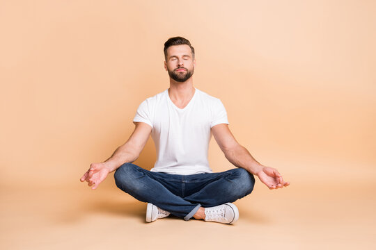 Portrait of nice calm focused guy sitting on floor meditating relaxation isolated over beige pastel color background
