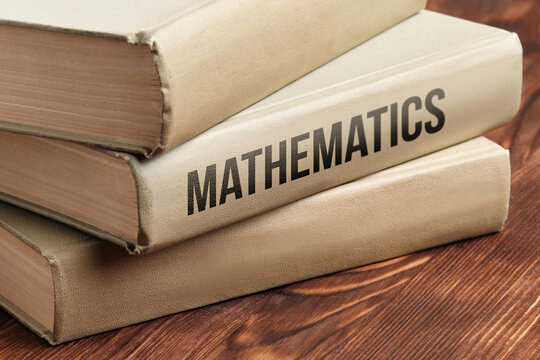 Mathematics subject book concept on a wooden table for learning.