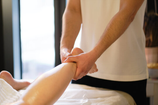Relaxing massage on the foot in spa salon indoors.