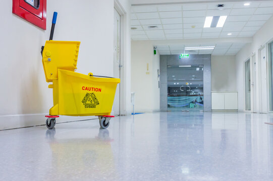 Mop bucket and wringer with caution sign on black floor in walkway office building