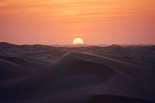 Sand dunes in desert landscape at beautiful sunset. Abu Dhabi, United Arab Emirates