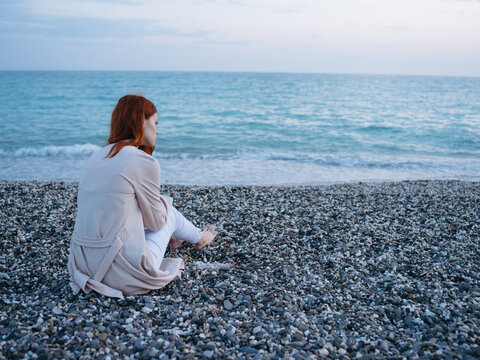 woman on a rocky beach in a sweater and pants and the ocean in the backgroun