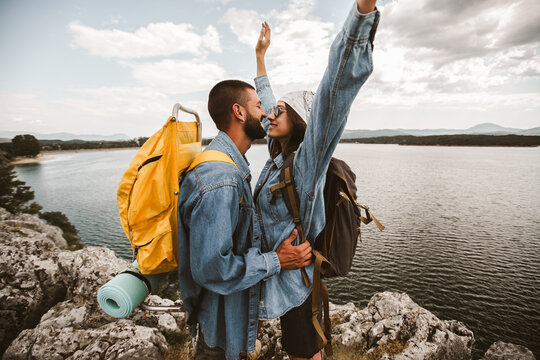 Beautiful couple of hikers in love are kissing enjoying in nature.