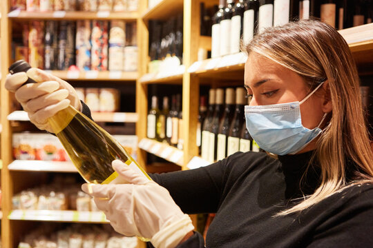Customer with mouthguard and gloves buying wine