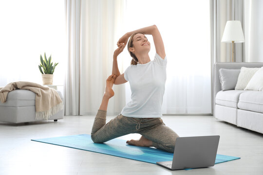 Woman having online video class via laptop at home. Distance yoga course during coronavirus pandemic