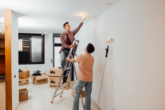 Young man on a stairway changing a light bulb while his friend helps to hold the ladder. Gay couple moved in a new home and is doing renovations. Apartment with cardboard boxes.