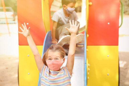 Little children with medical face masks on playground during covid-19 quarantine