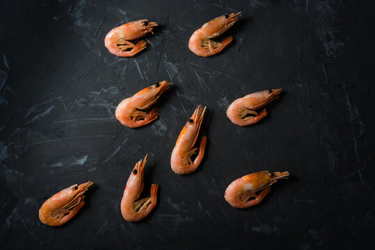 a bunch of boiled shrimp on a black background