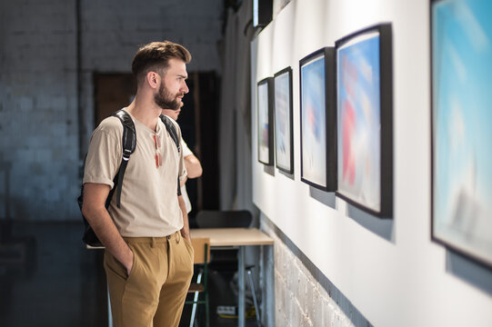 Young man in modern art exhibition gallery hall contemplating artwork. Abstract painting