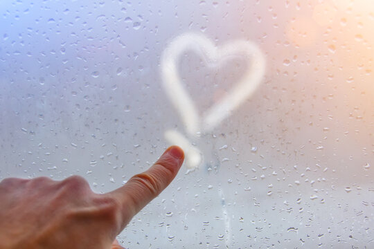 A hand and a finger draws a heart on the misted glass, sensuality, love for loved ones, soul mate.