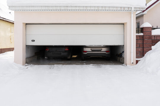 xterior of a garage attached to a house. garage with two cars inside in winter. semi-open sectional doors