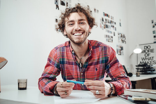 Happy man in shirt with a pencil poses in comfortable office sitting at table and looking at camera.