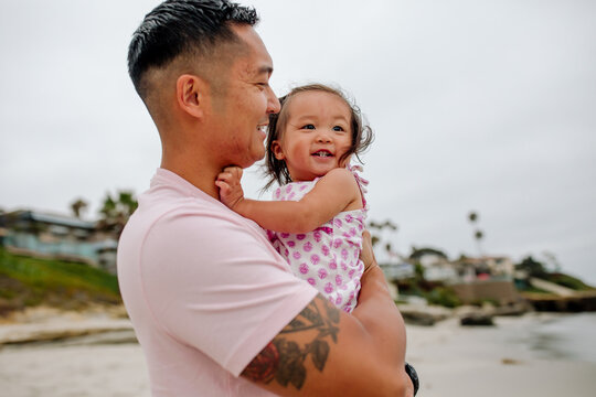 Asian dad with tattoo holding happy year-old daughter at beach