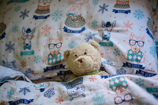 A child's stuffed bear toy lays lovingly tucked into cozy bed