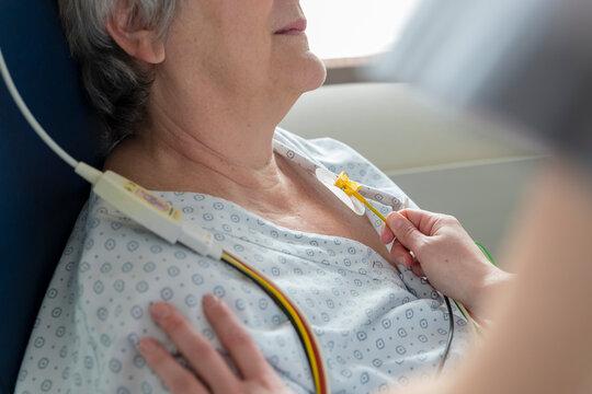 a nurse places electrodes on a patient's chest