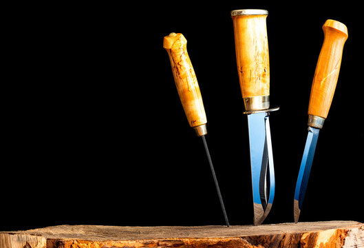 Three hunting knives are stuck in a birch stump. The knives have wooden handles. Horizontal photo on a black background.