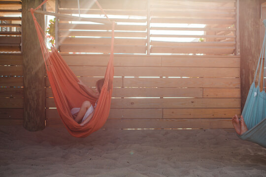 small children relax in colorful hammocks at beach in golden light