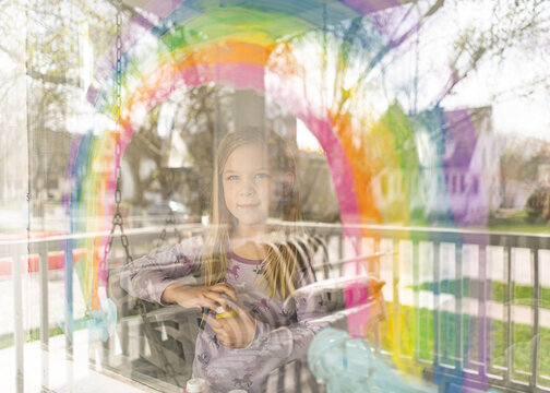 outside of window view of girl painting rainbow on window
