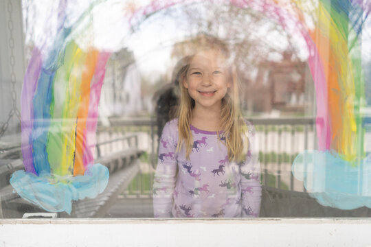 smiling blond young girl under rainbow painted on window