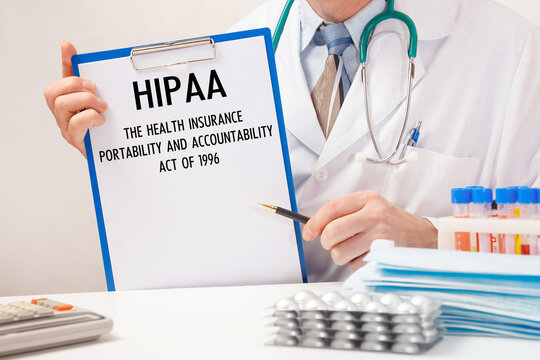 Doctor holds paper with inscription HIPAA The Health Insurance Portability and Accountability Act of 1996