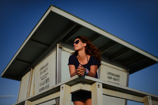 Young woman looking at sea from lifeguard tower