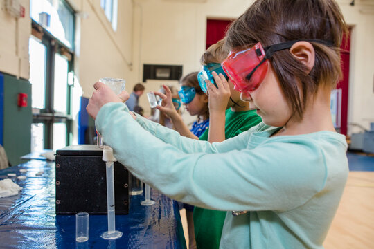 A little girl in safety goggles measures liquid into a test tube