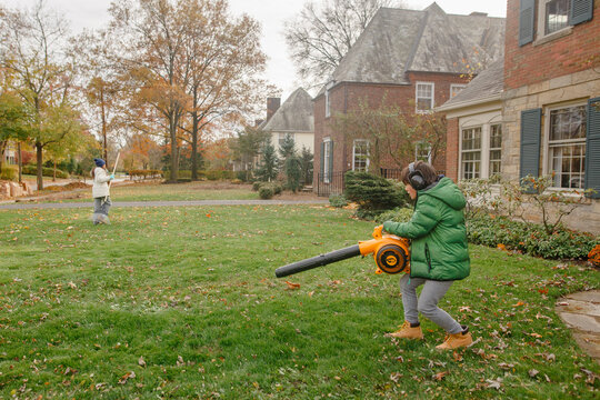 A boy clears leaves off lawn with leaf blower while girl rakes