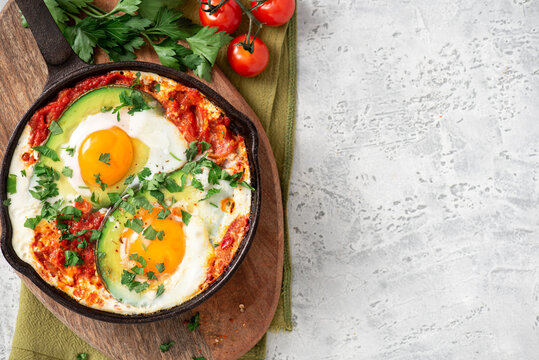 Shakshouka with avocado in a frying pan on a gray table top view. Shakshouka of tomato sauce, eggs, spices, onions, garlic, and avocado. Tasty Maghreb style breakfast. Copy space for text.