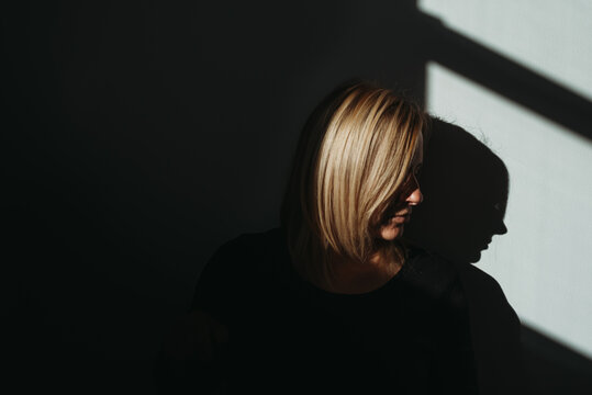 Woman's profile in bright light with black background and shadows