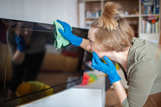 Woman cleans home, wipes dust from tv screen and looking at self reflexing, authentic inner life