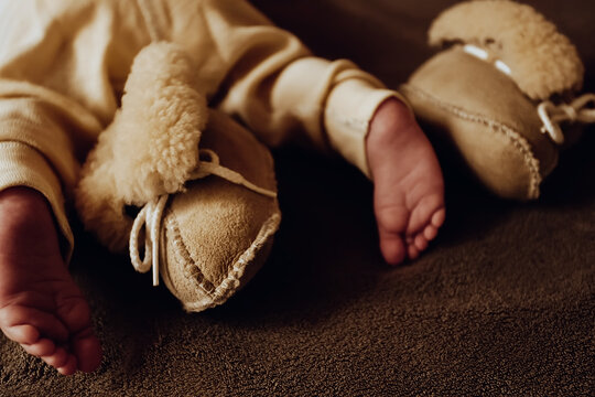 Toes of newborn baby with beige sheepskin booties and thermo pants