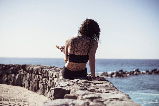 fit woman with tree tattoo sits by edge of ocean with cute dog on lap