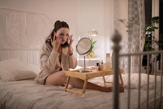 Young female spreading moisturizing mask on face